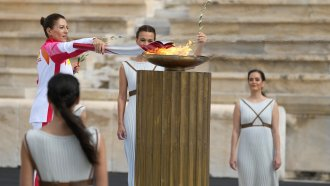 Greece's Olympic Cross Country Ski Champion lights the flame during the Olympic flame handover ceremony