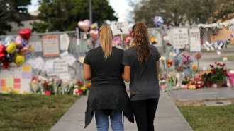 Two people stand in front of a makeshift memorial.