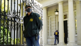 FBI agents stand in front of a home of Russian oligarch Oleg Deripaska following a raid.
