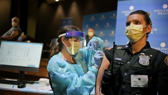 A police officer receives a COVID-19 vaccine