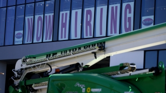 A hiring sign is displayed at a furniture store window
