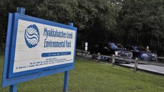 Florida police officers block the entrance to the Myakkahatchee Creek Environmental Park.