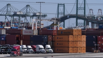 Trucks line up next to containers at the Port of Los Angeles