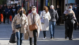 Shoppers wearing face masks walk on Oxford Street in central London.