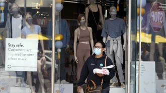 A woman walking out of a store with a mask on.