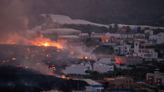 Lava flows from the Cumbre Vieja volcano, destroying houses
