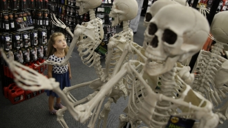A girl looks at the Halloween skeletons at a retail store.