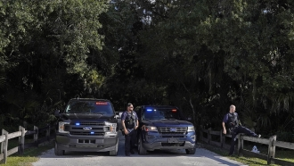 North Port police officers block the entrance to the Myakkahatchee Creek Environmental Park