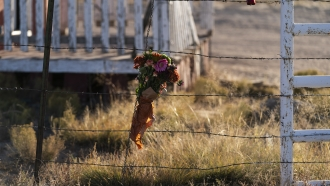 """A bouquet of flowers hangs from a fence on the set of the movie """"Rust"""""""