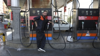 A gas station worker leans against a pump that has been turned off in Tehran, Iran.