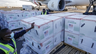 An airport worker stands next to boxes of Moderna coronavirus vaccines