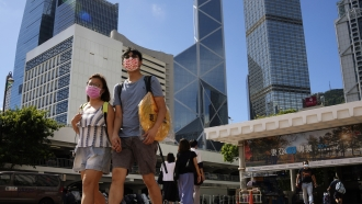 A couple walk along a street in Central business district in Hong Kong