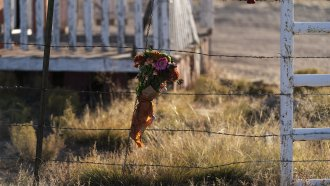 A bouquet of flowers is left on a fence outside the Bonanza Creek Ranch