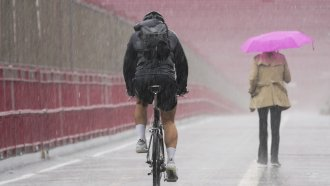 A pedestrian and cyclist make their way over a bridge in pouring rain