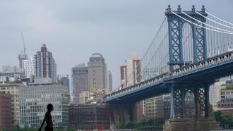 A pedestrian walks in front of the Brooklyn skyline and Manhattan bridge