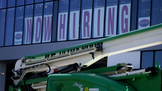 A hiring sign at a store.