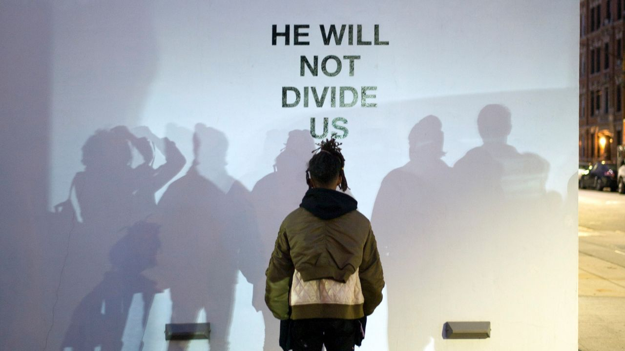 "Jaden Smith faces a wall with the words ""he will not divide us"" printed on it."