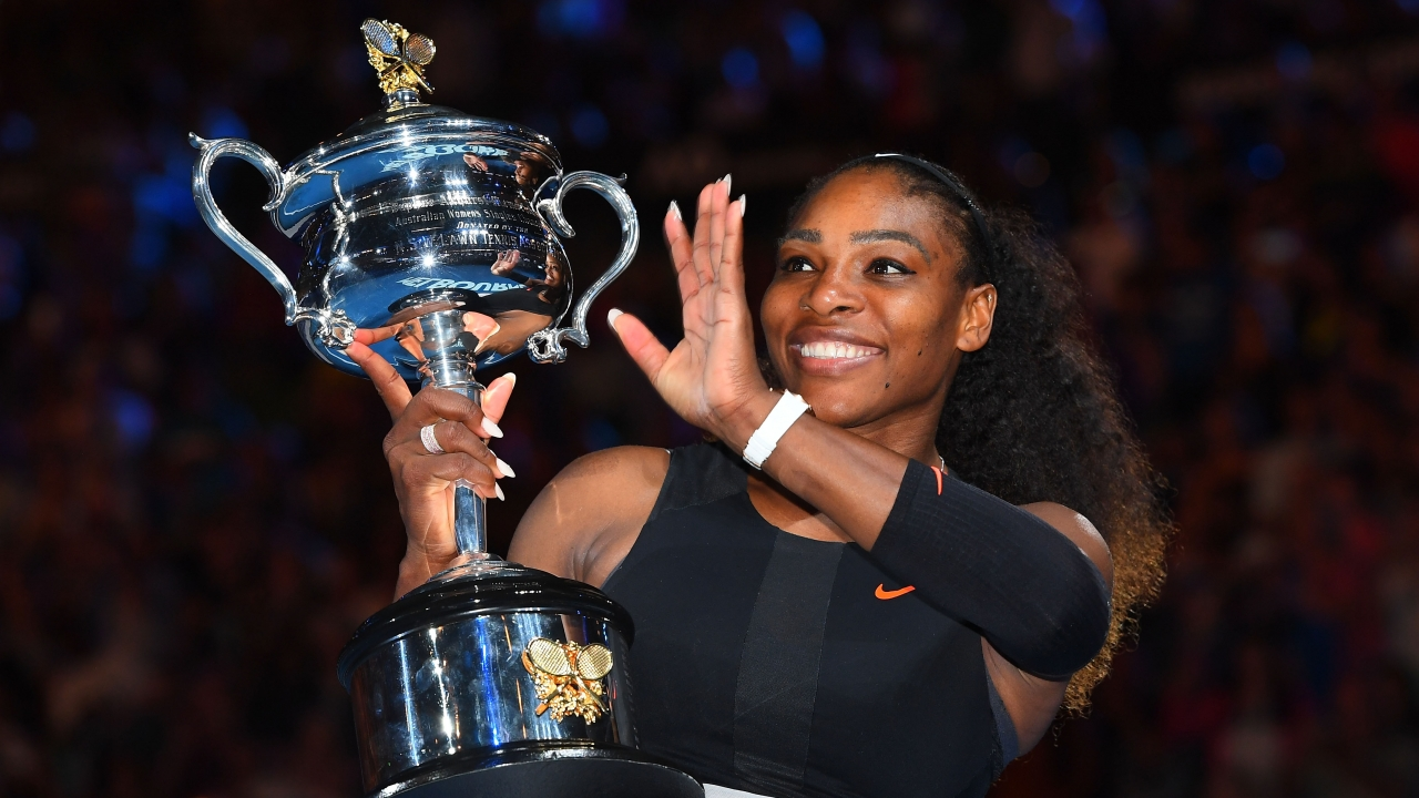 Serena Williams waves while holding the trophy after her Australian Open win.