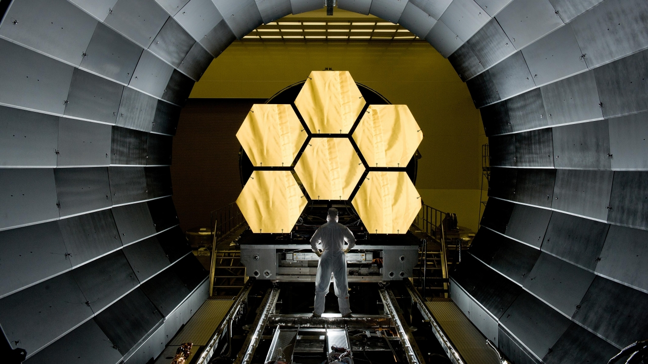 Engineer stands in front of James Webb telescope's first few mirrors