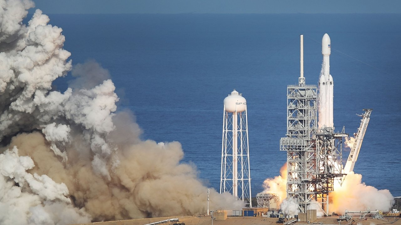 SpaceX's Falcon Heavy lifting off amid a dust cloud