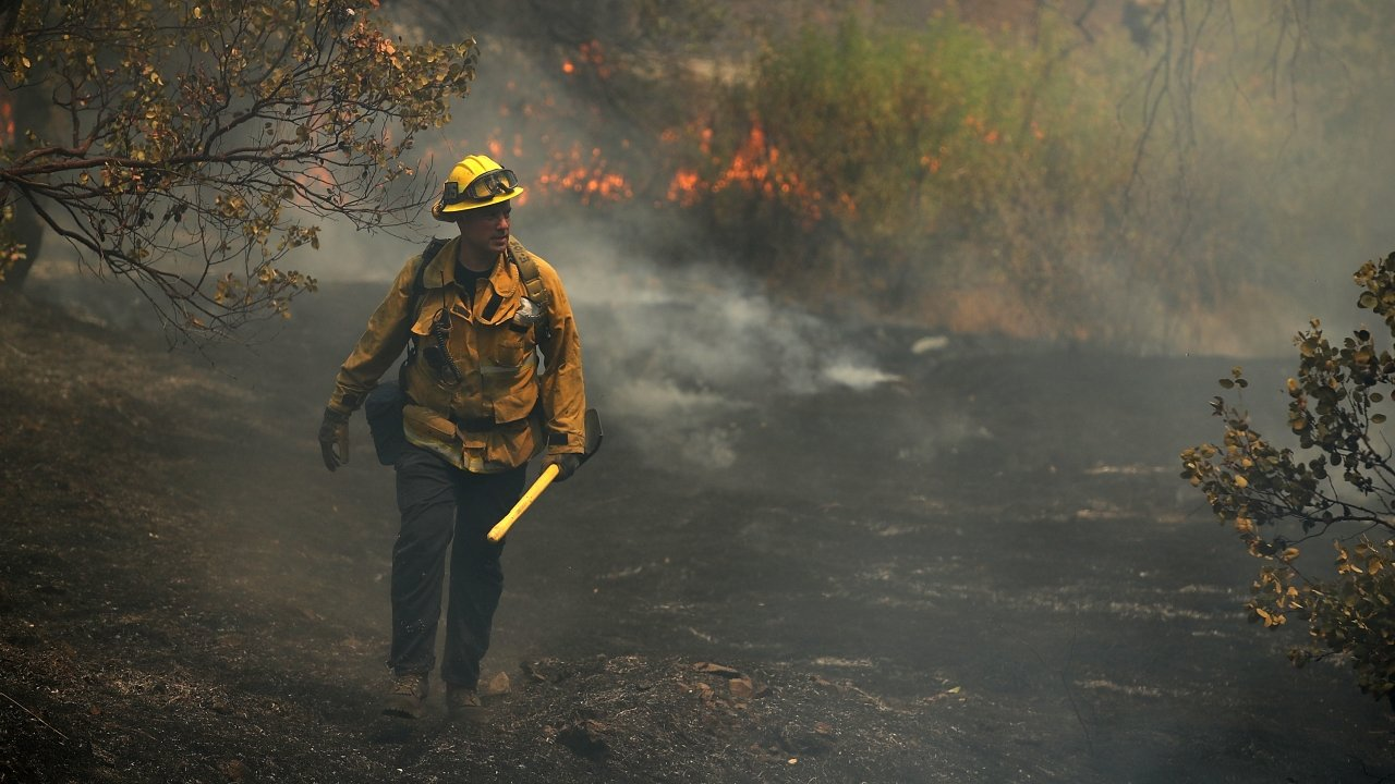 A Los Angeles city firefighter walks through a field burned by the Carr Fire