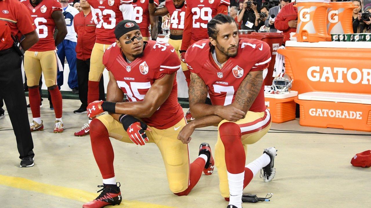 Colin Kaepernick kneels with teammate