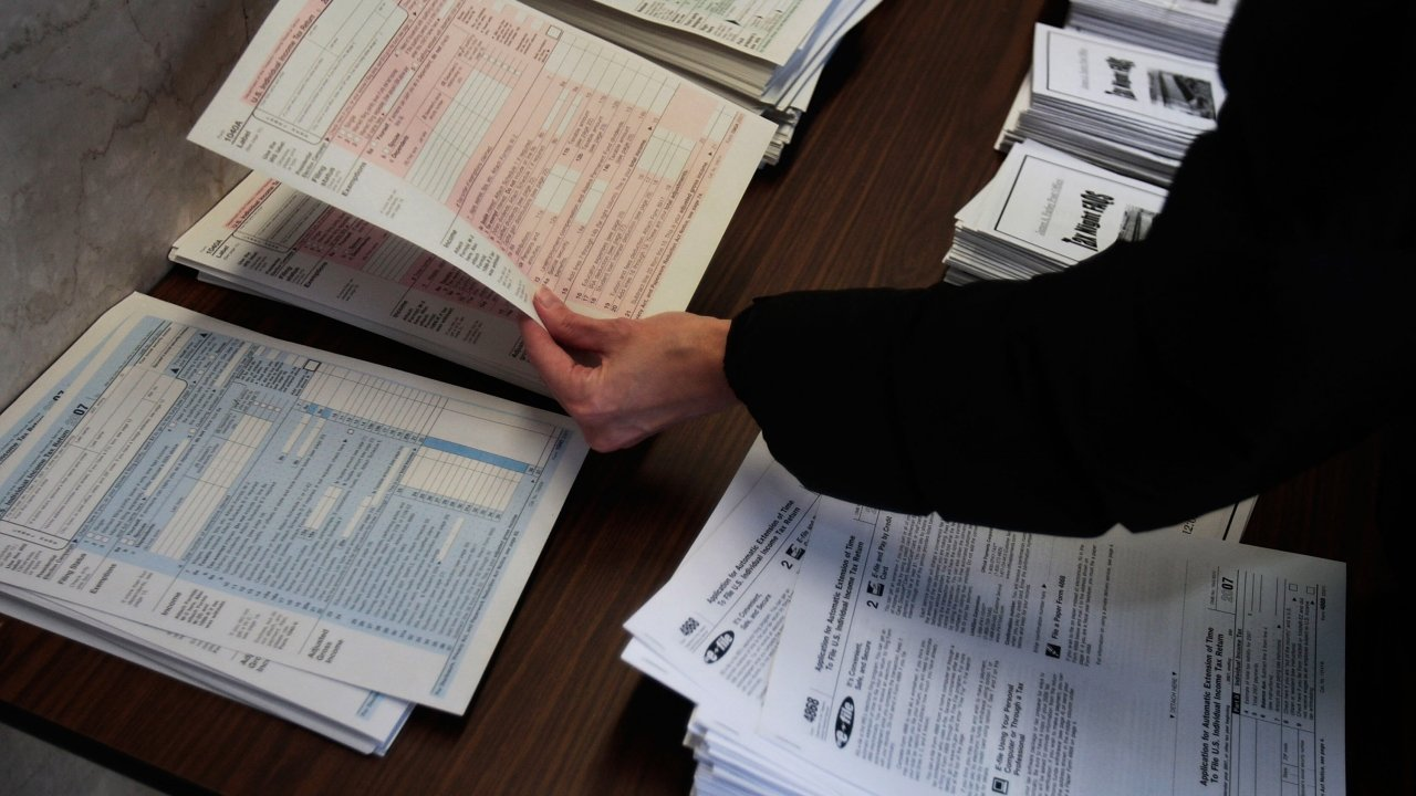 A person picks up tax forms from a table