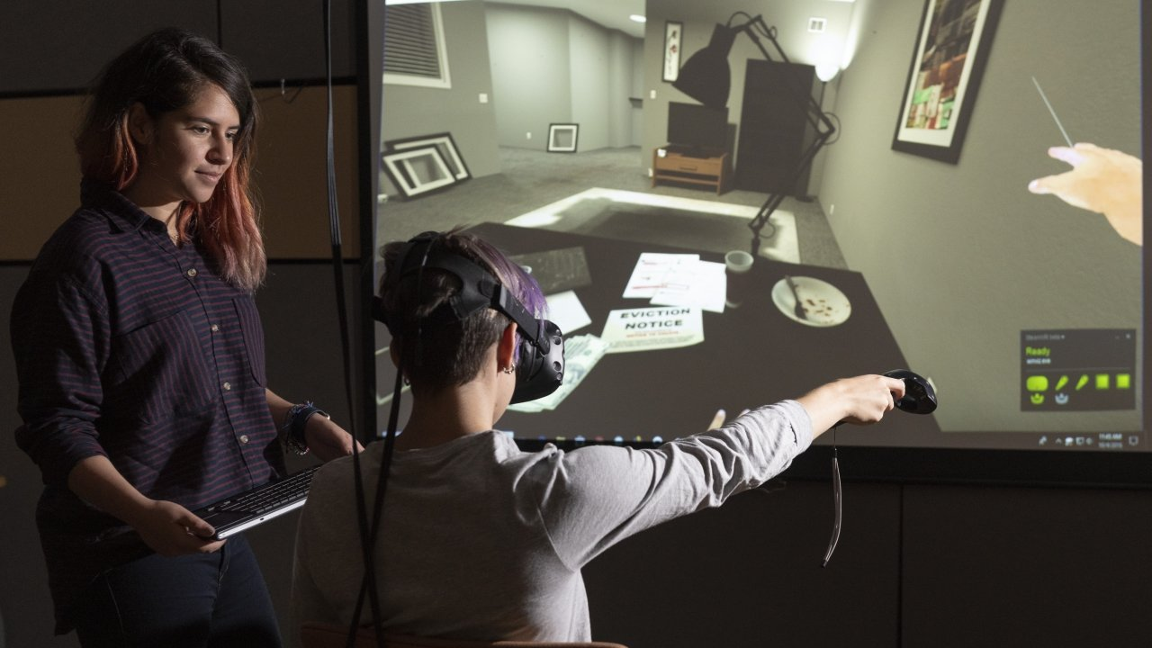 Stanford University researcher Fernanda Herrera, left, watches as fellow student navigates through the VR experience.
