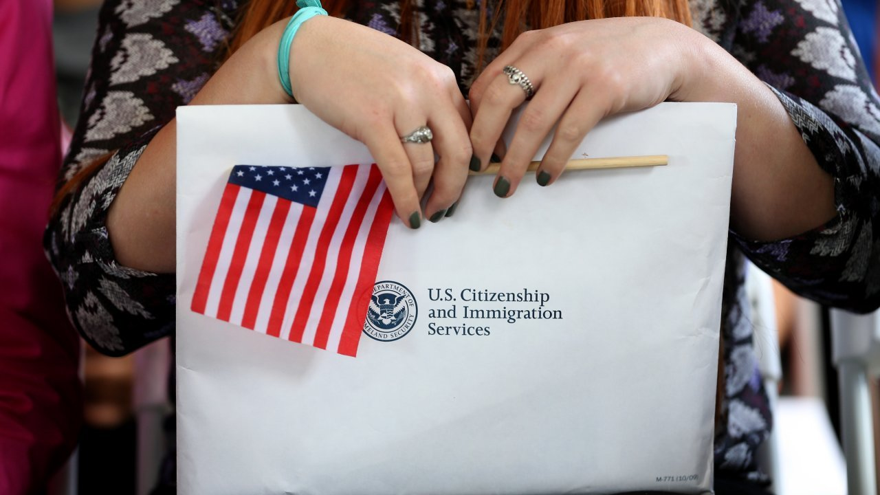A woman holds an American flag and a U.S. Citizenship and Immigration Services envelope