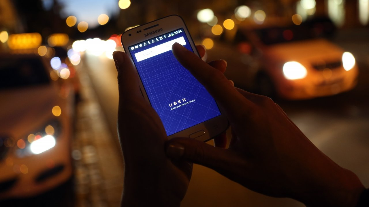 A woman uses the Uber app.