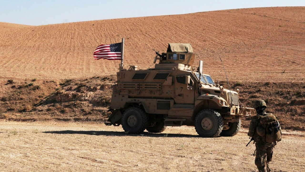 A U.S. Soldier walks toward a tactical vehicle used to provide security during a patrol outside Manbij, Syria.