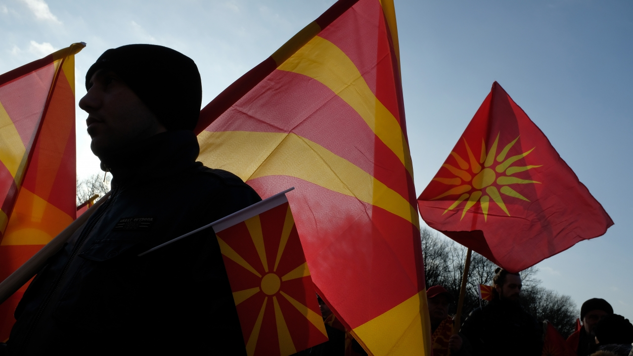 Macedonians hold Macedonian flags during a protest