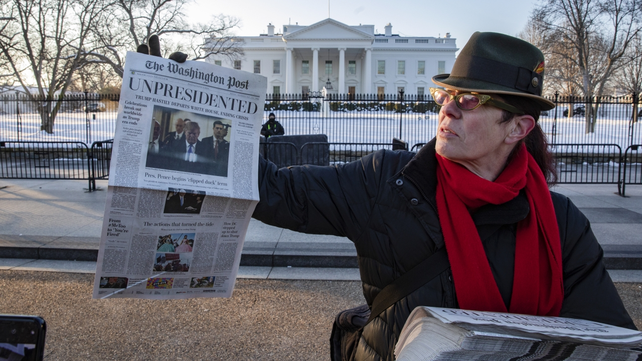 """Volunteers distribute a lookalike """"special edition"""" of The Washington Post."""