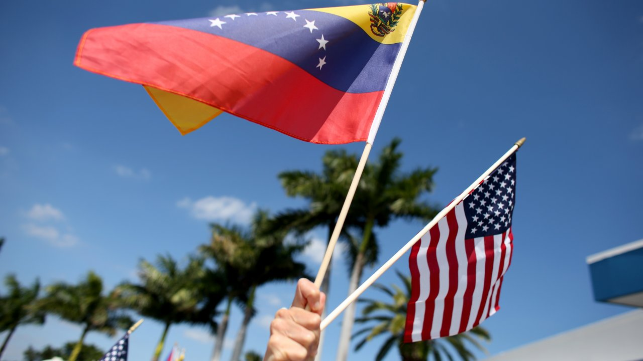A protester holds Venezuelan and American flags
