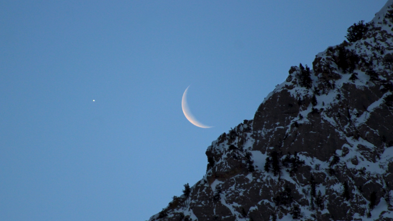 A waning crescent moon rises above the Wasatch Mountains by Salt Lake City, UT