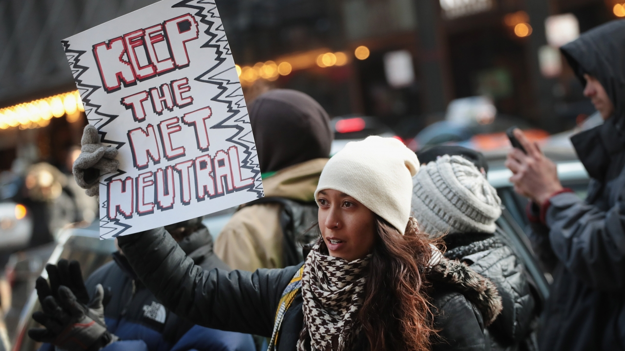 A demonstrator protests the Federal Communications Commission outside a Verizon store in Chicago, Illinois
