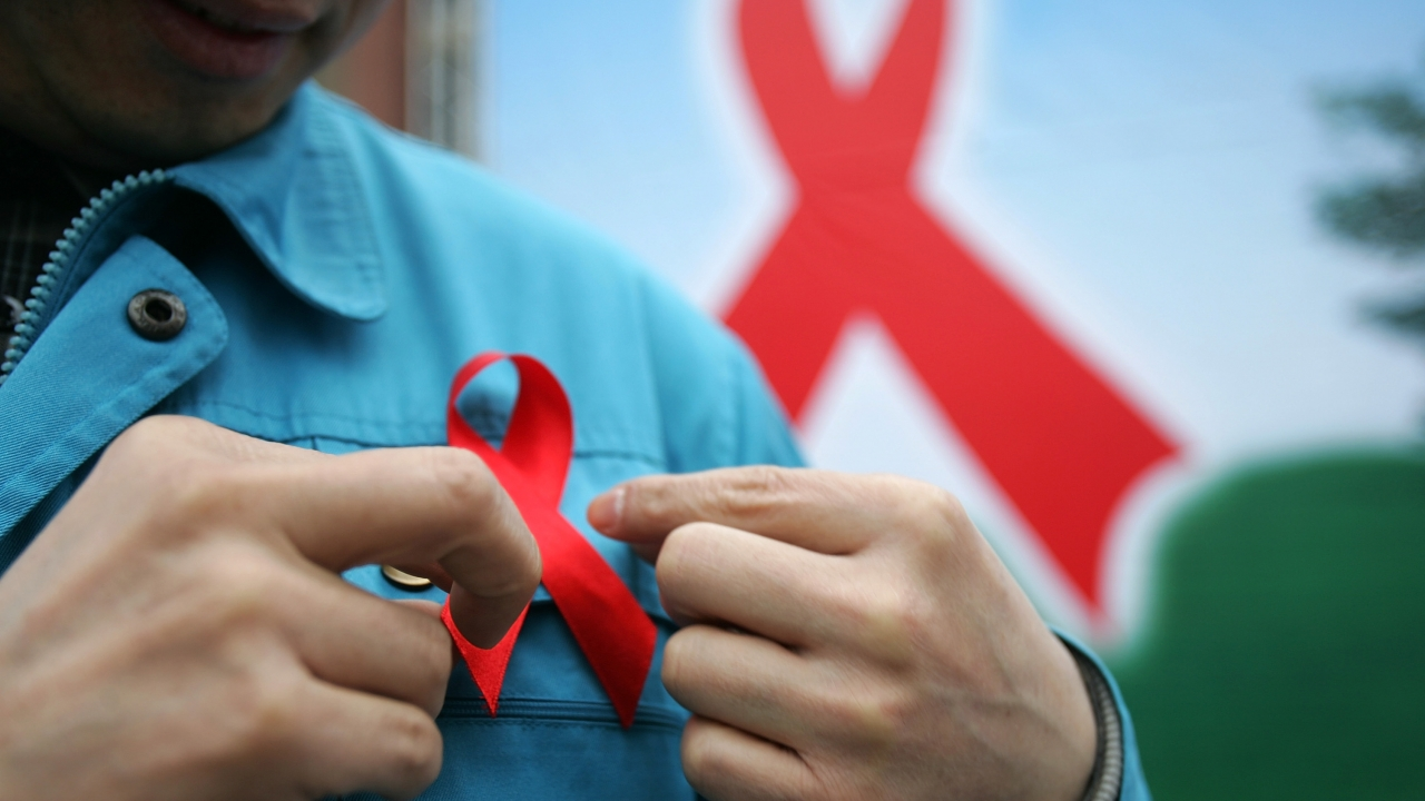 A person wears a red HIV/AIDS awareness ribbon