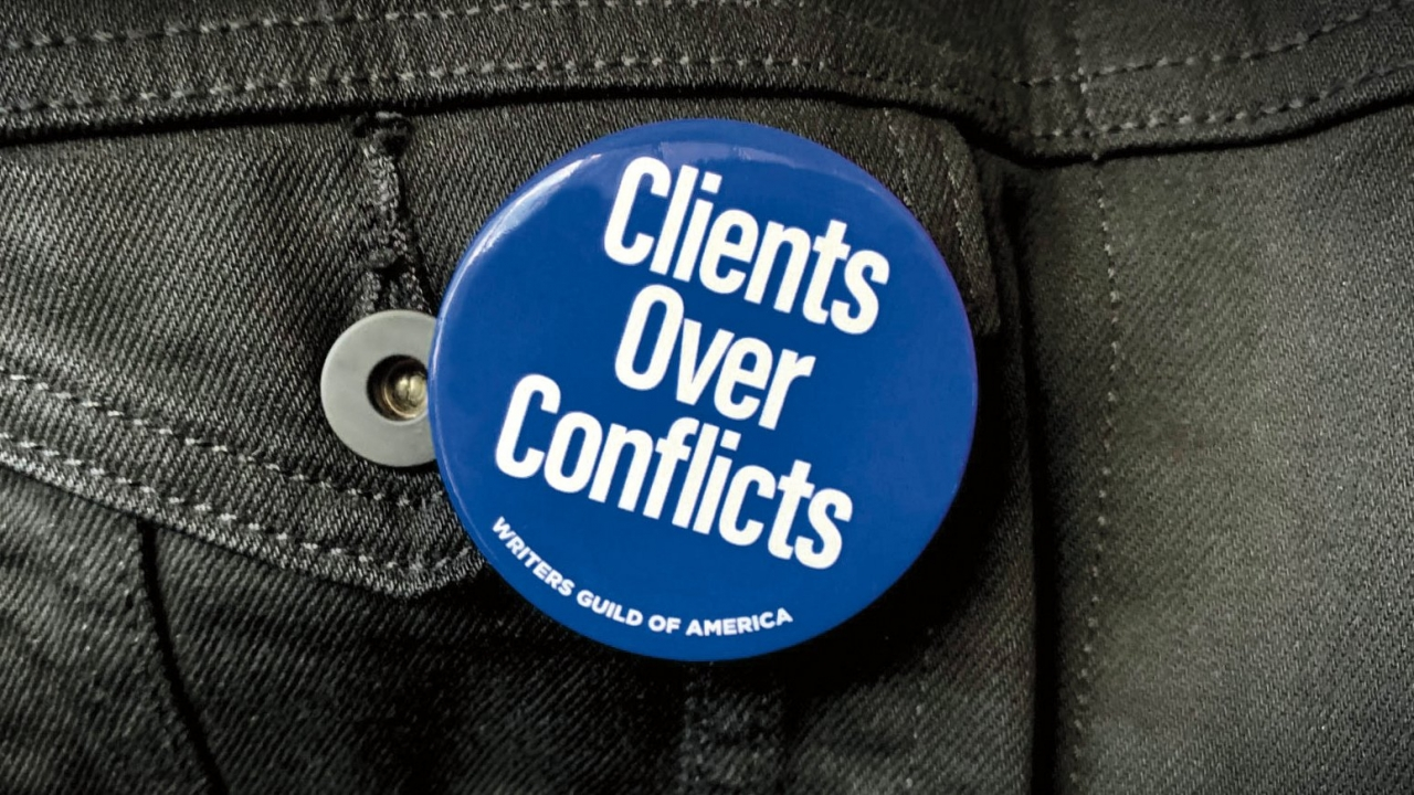 "A Writer's Guild of America button says: ""Clients Over Conflicts"""