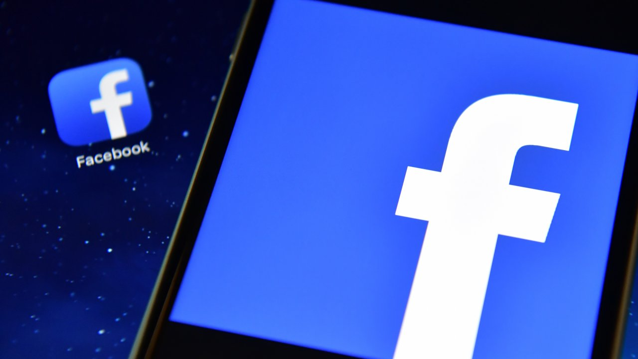 A tablet with the Facebook logo sits on top of another device displaying the Facebook App