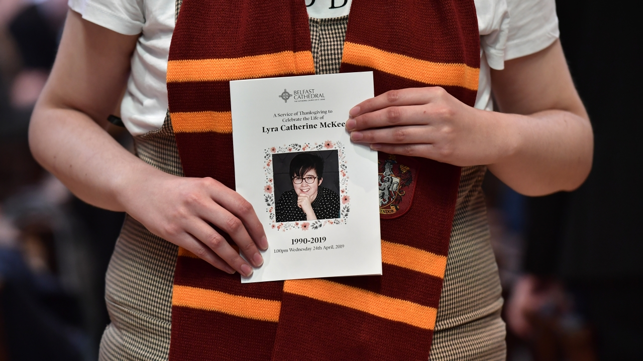 A mourner wearing a Hogwarts scarf holds the order of service for the funeral for journalist Lyra McKee