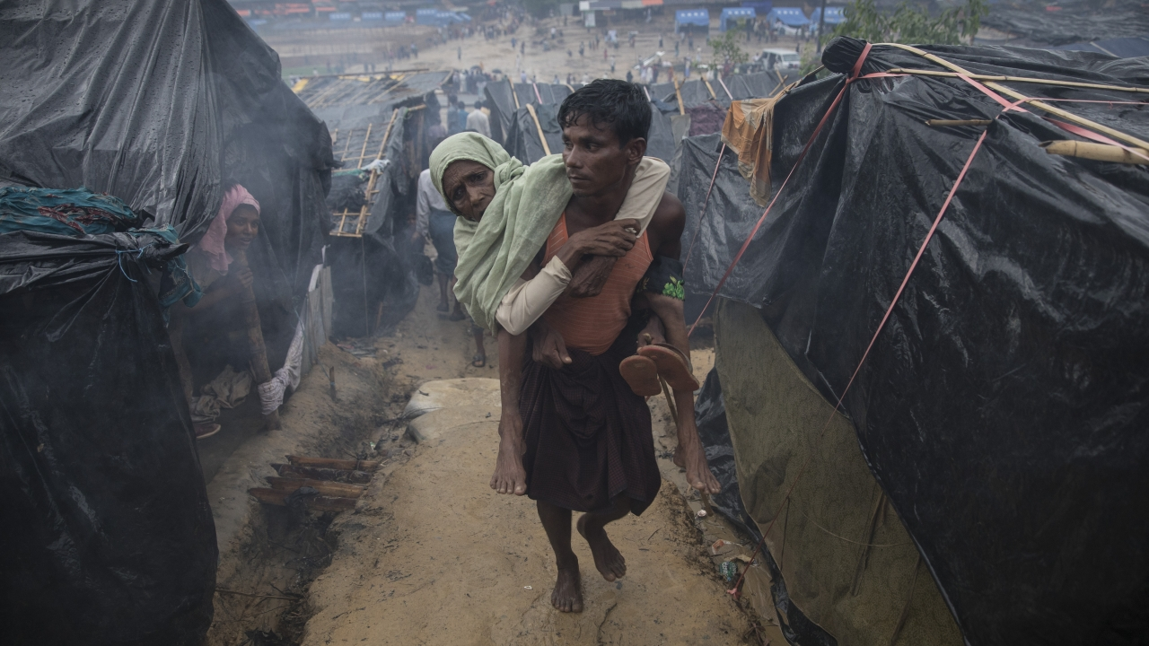 A Rohingya man carries a woman on his back