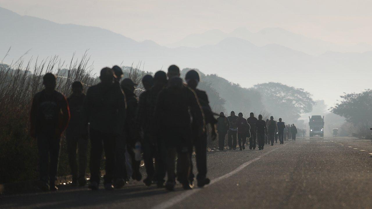 People from a caravan of Central American migrants walk alongside a highway.