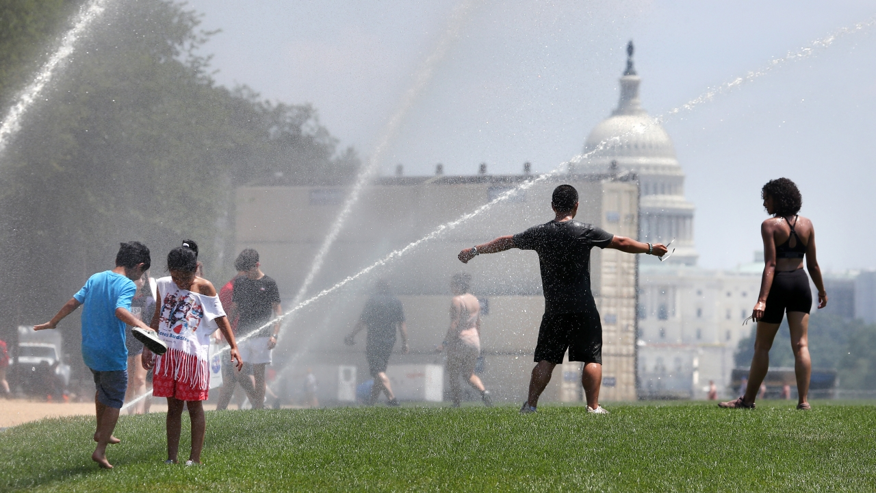 People cool off at open sprinklers on the National Mall, on July 19, 2019 in Washington, DC