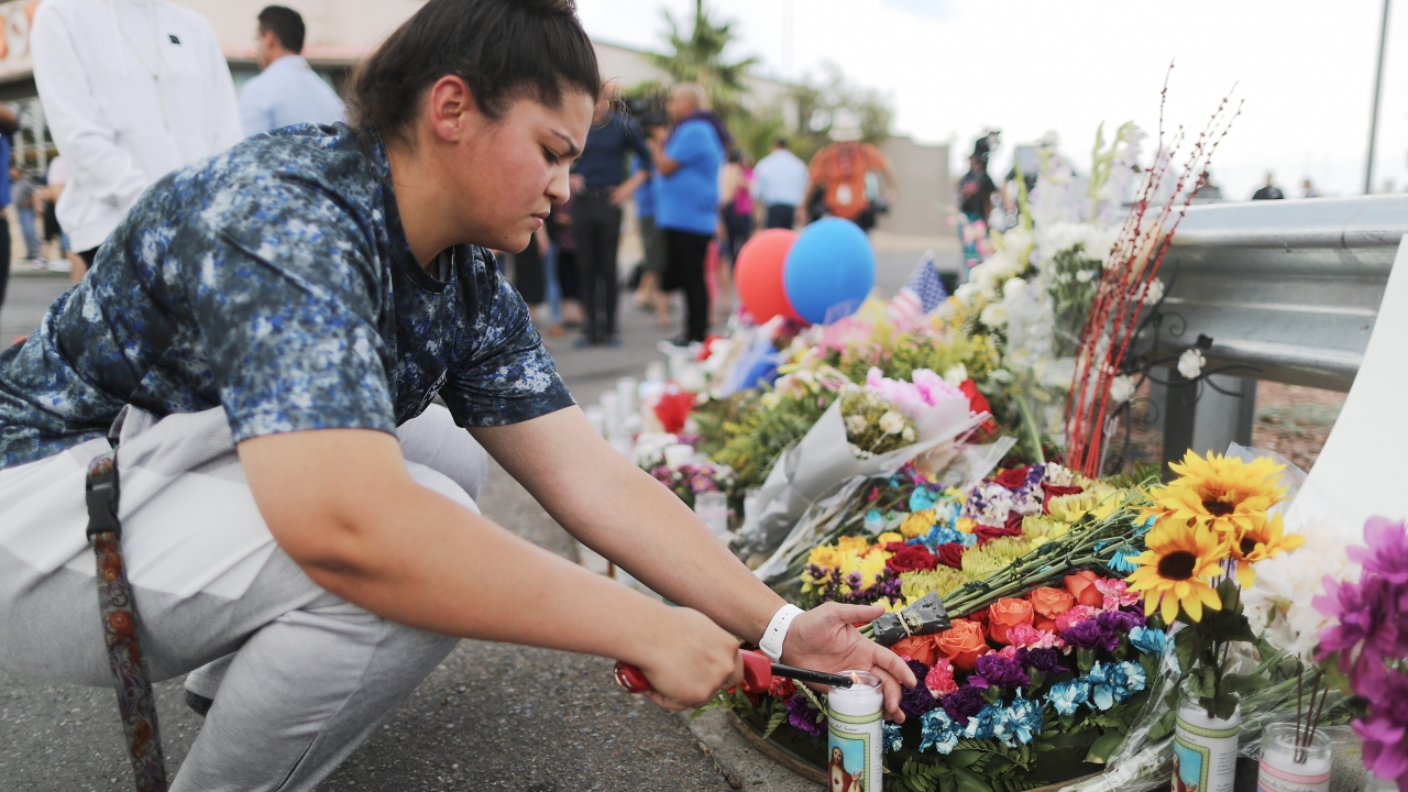 A woman lights a candle at a make-shift memorial in El Paso, Texas