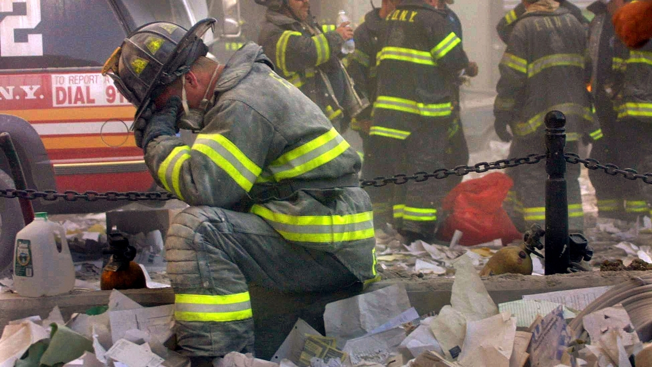 A firefighter kneels and covers his face at the rubble of the World Trade Center in 2001.
