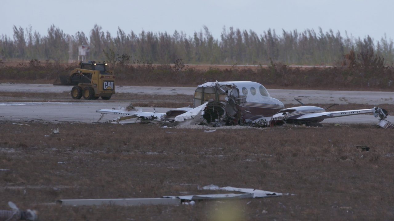 A destroyed airplane sits near the runway at Freeport's airport.
