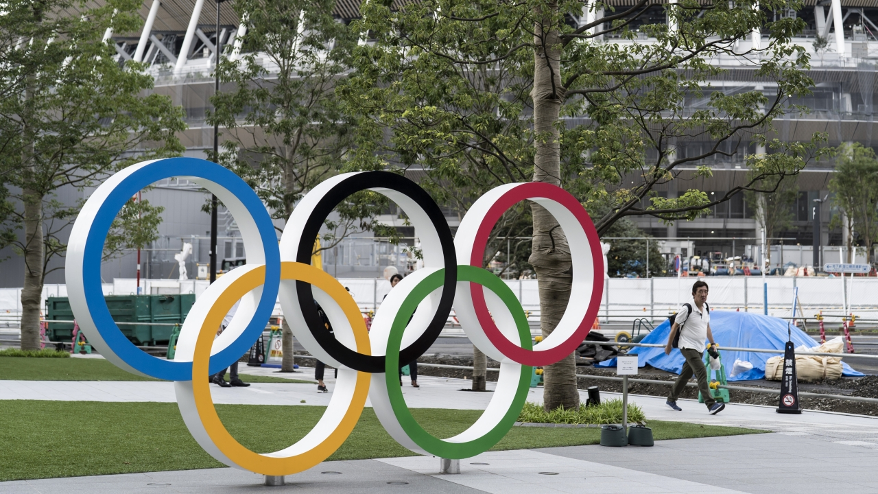 A man looks at the Olympic rings displayed in front of the New National Stadium, the main venue for the Tokyo 2020 Olympics