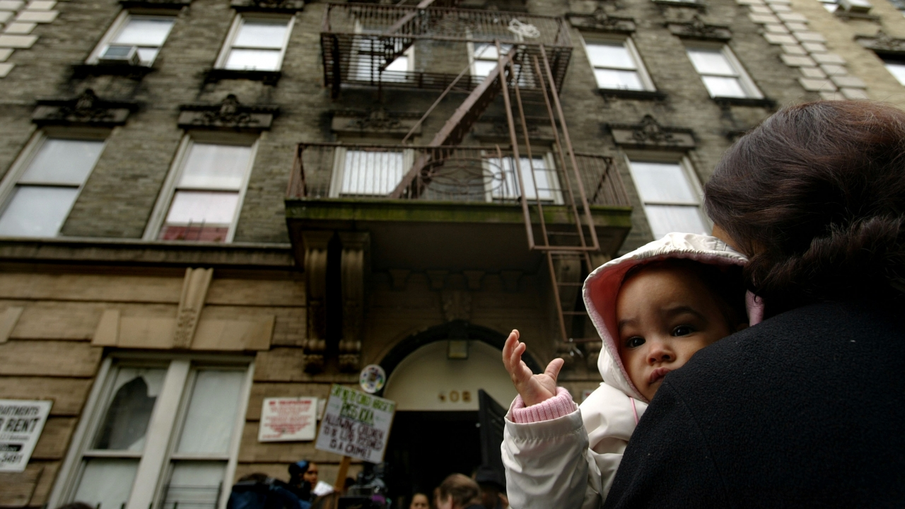 Woman holds baby outside apartment in New York City