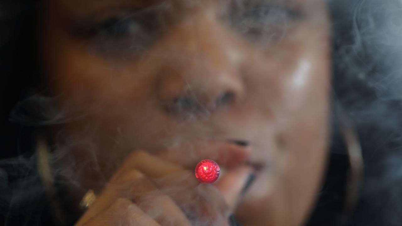 A woman smokes an E-Cigarette