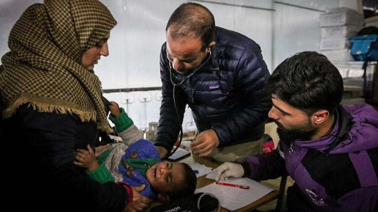Syrian-American humanitarian doctor Zaher Sahloul treats a baby at a camp for displaced people in Idlib, Syria.